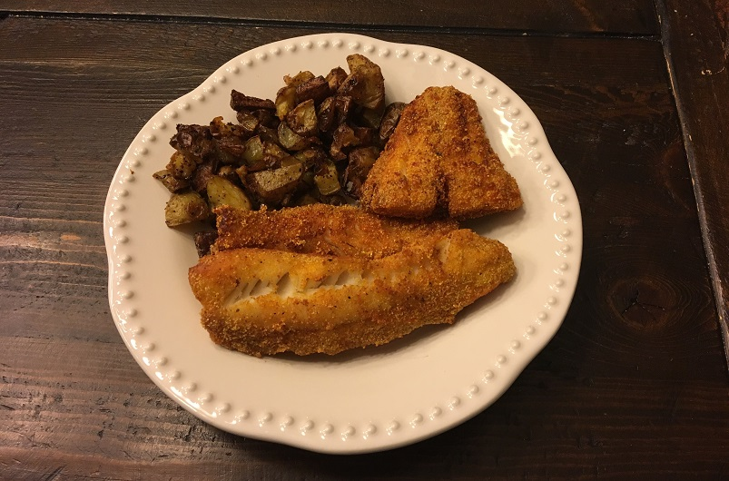 Fried walleye and roasted potatoes on a dinner plate