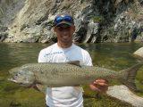 Jordan Rodriguez holding a large Chinook salmon