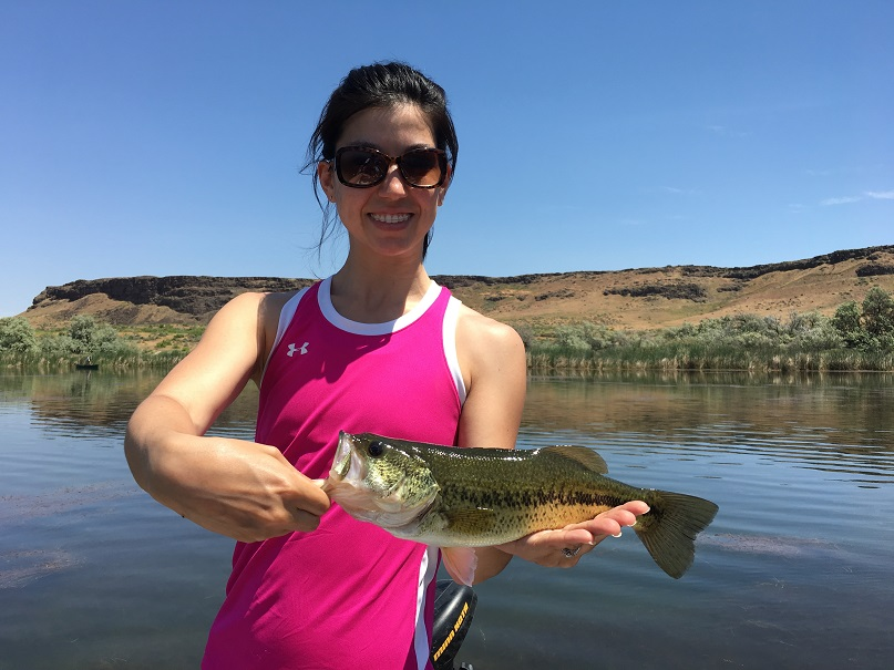 Happy female student holding a largemouth bass