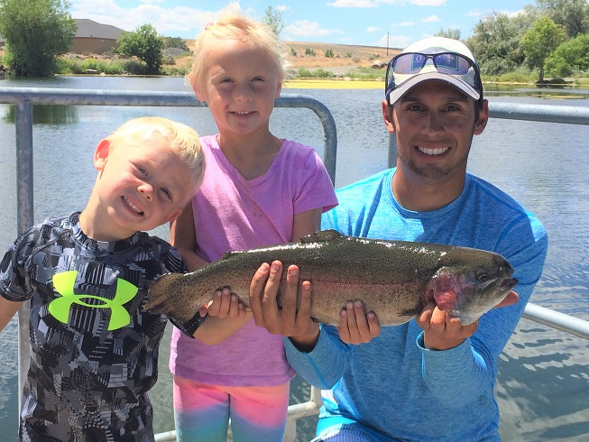 Young boy, young girl and Jordan Rodriguez posing with a huge rainbow trout