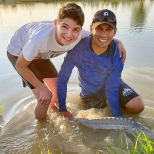 A teenaged boy and Jordan Rodriguez holding a white sturgeon.