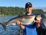 Jordan Rodriguez holding a large Chinook Salmon.