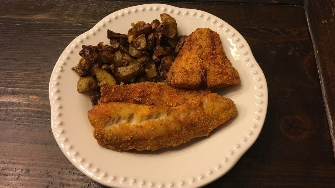 A plate featuring two fried fish fillets and roasted potatoes
