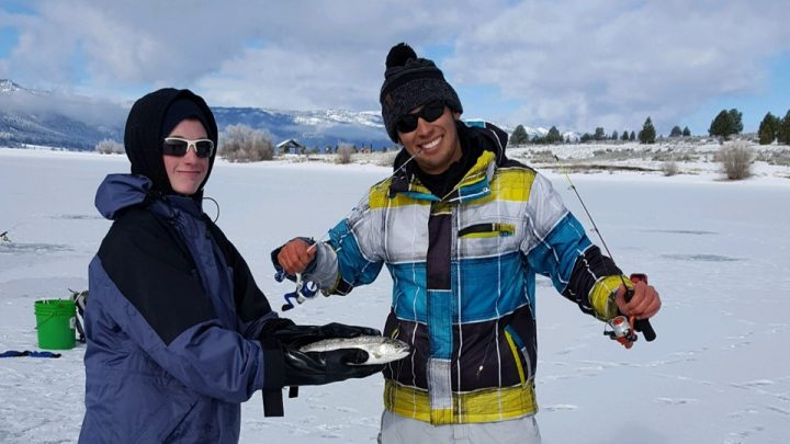 Jordan Rodriguez and Justin Maxwell show off a rainbow trout that nearly stole a rod on an ice fishing trip.