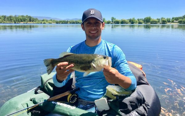 Jordan Rodriguez shows off a largemouth bass caught on a fly rod