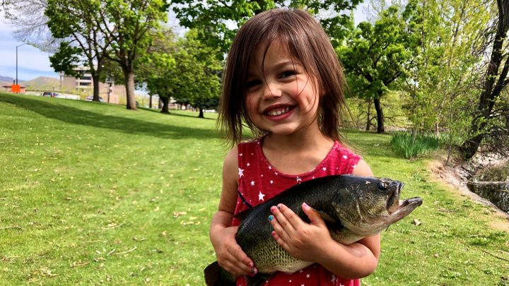 Quinn Rodriguez holds on tight to a big largemouth bass caught in a local pond.