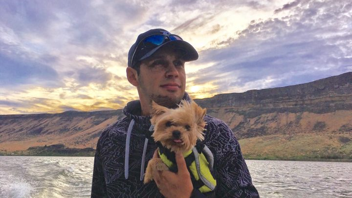 Jordan Rodriguez boats through the Snake River Canyon holding his best fishing buddy, Yorkshire terrier Winston